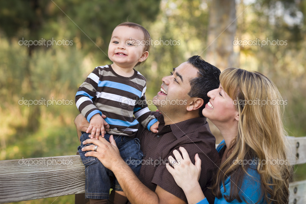 Happy Mixed Race Ethnic Family Playing In The Park
