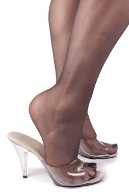 Femal legs wearing tights and clear high heels over white backgr