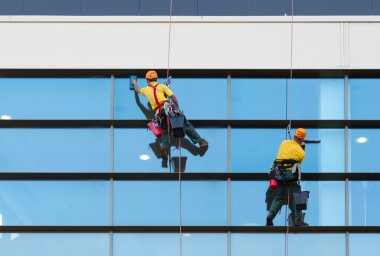 Two workers washing windows