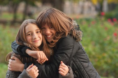 Teenage girls hugging each other in the park on the beautiful autumn day