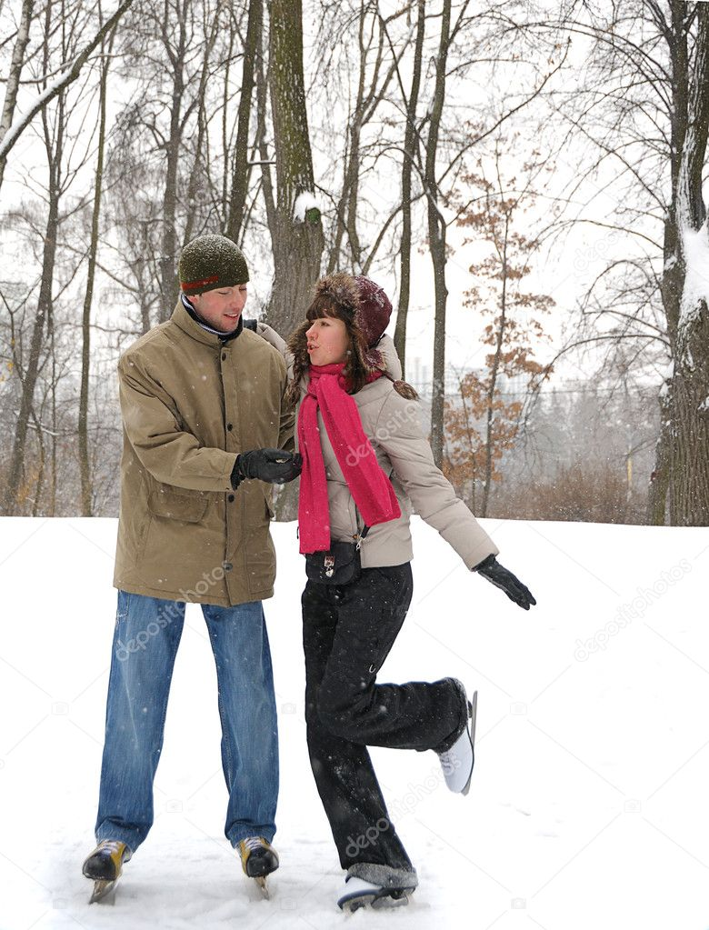 Young couple in winter skate rink