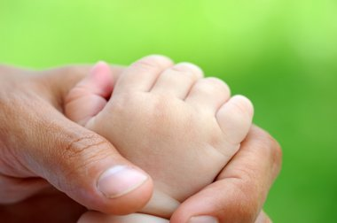 Child's hand is in a paternal hand