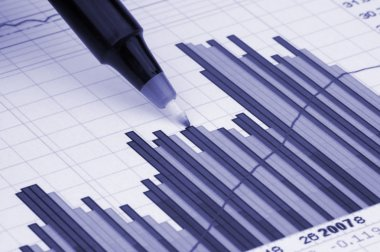 Pen showing diagram on financial report or magazine