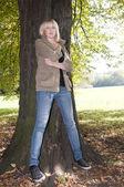 Mladá žena stojí na stromě