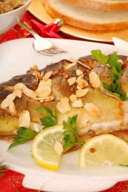 Carp baked with almonds on christmas table