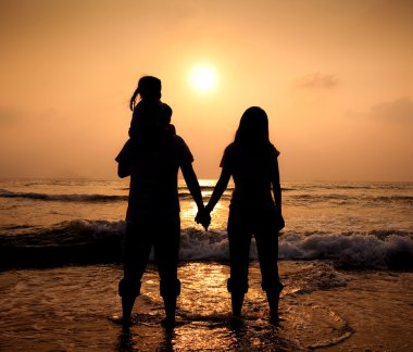 The silhouette of loving asian family walking while holding hands on beach