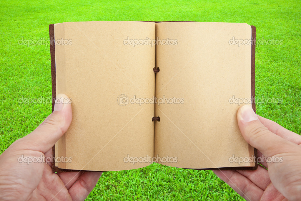 Opened book in hand on the grass field