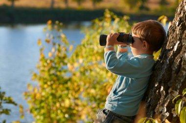 Little boy looking through binocular