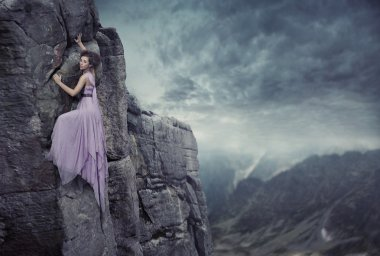 Conceptual photo of a woman climbing to the top of a mountain