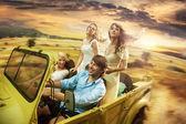 Gruppe fröhlicher Freunde, die ein Cabriolet fahren