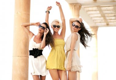 Three cheerful women wearing sunglasses