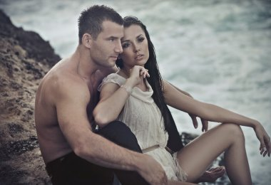 Cute couple sitting on rocks
