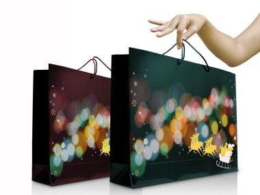 Girl hand pick up the green christmas shopping bag
