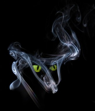 Green cat eyes in a smoke