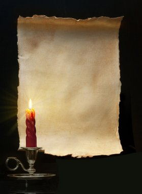 Vintage paper scroll lit a candle