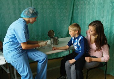 A doctor at the clinic makes injection syringe child