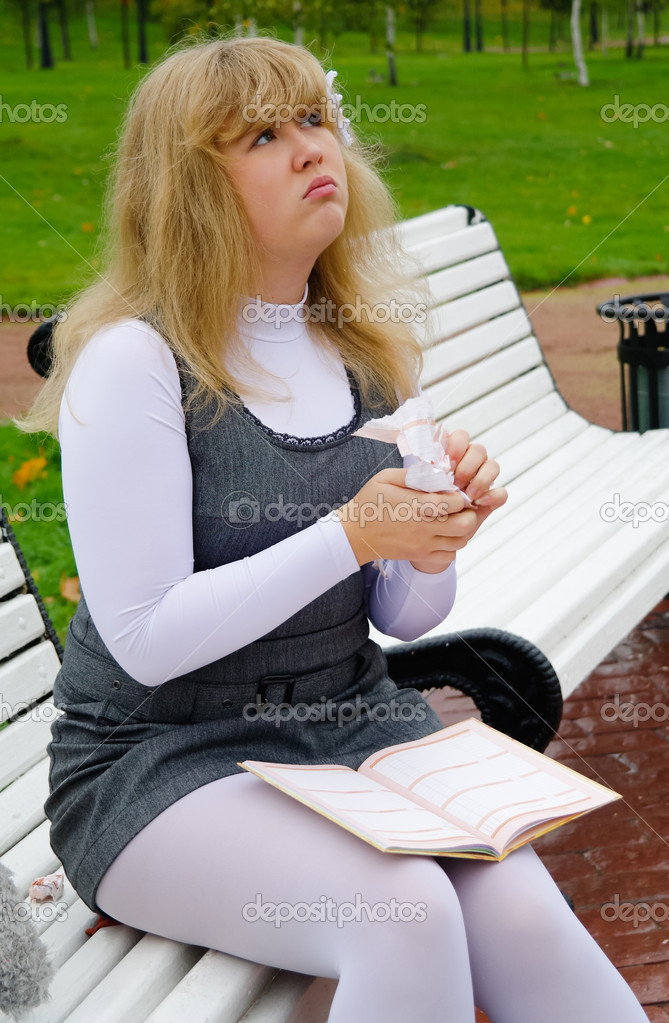 The schoolgirl sitting on a bench and tore pages of the diary