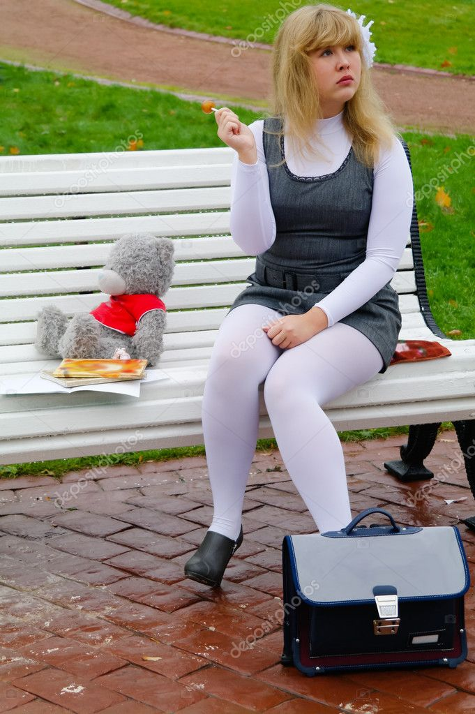 The schoolgirl sitting on a bench with a white candy