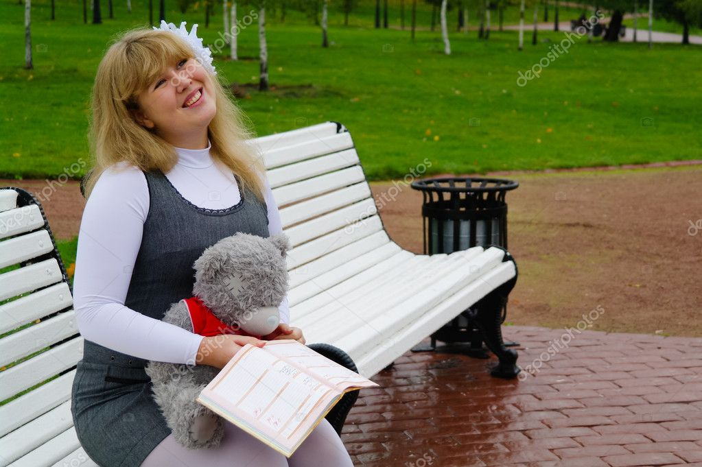 The schoolgirl sitting on a bench, Autumn Park, Moscow