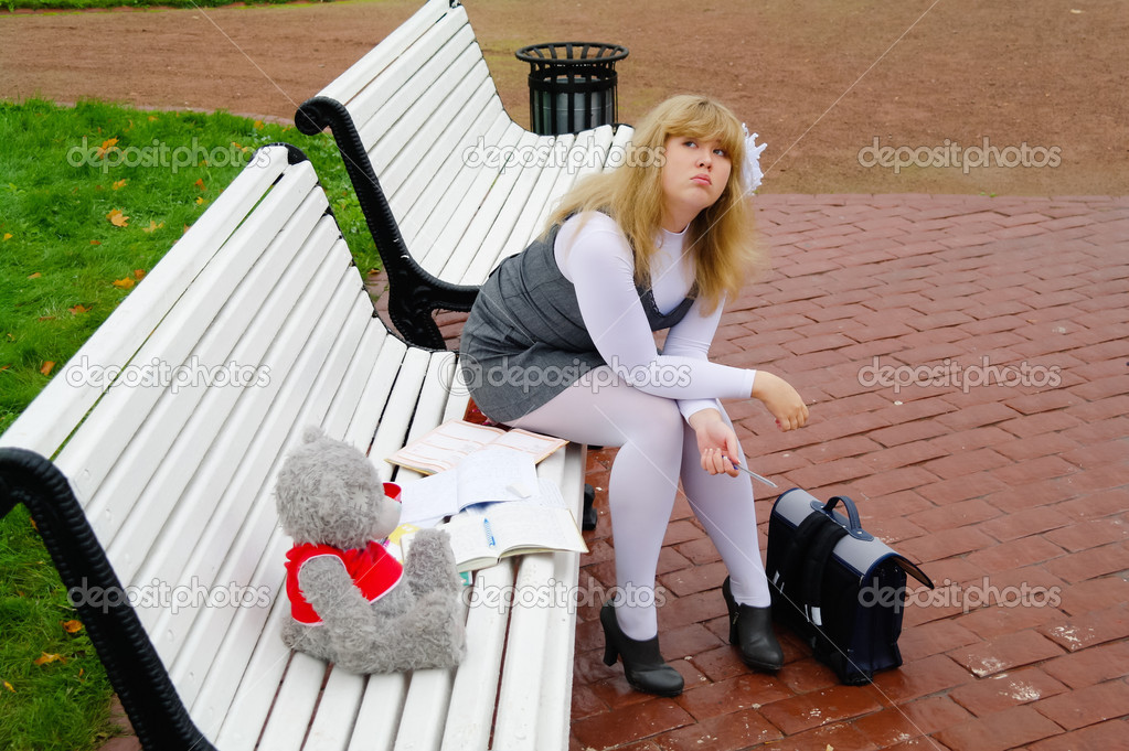 The schoolgirl sitting on a bench in Autumn Park