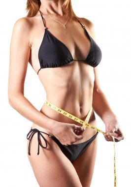 Slim woman measuring waist with tape measure in inches