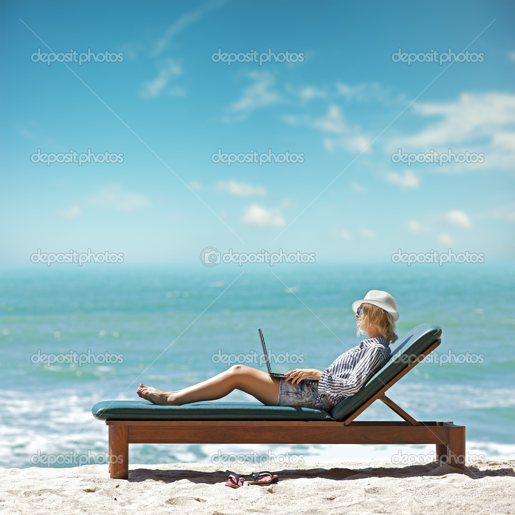 Young woman with laptop at the beach