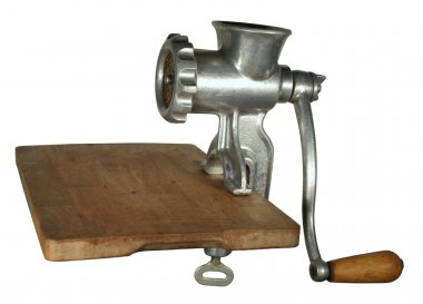 Classical meat grinder on a wooden cutting board.
