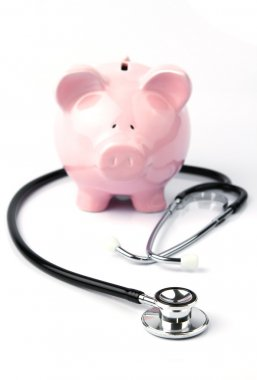 Piggy bank and stethoscope on white