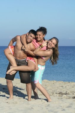Smiling group of youth, kids,or teenagers playing, piggyback on beach summe