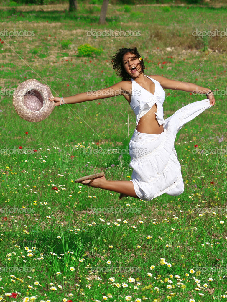 Happy healthy young woman jumping in summer or spring