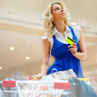 Photo of young joyful woman with shopping bags inside mall