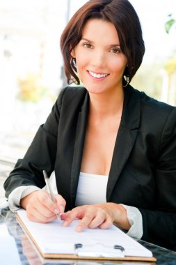 Closeup portrait of pretty woman sitting at cafe and signing doc