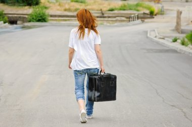 Young girl with suitcase walking down the street. Rear view