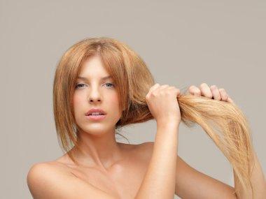Woman pulling dry hair split ends