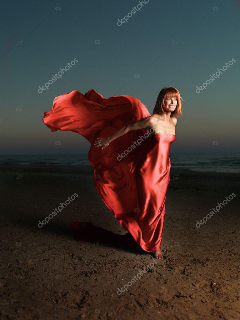 Woman on beach wind blowing fabric