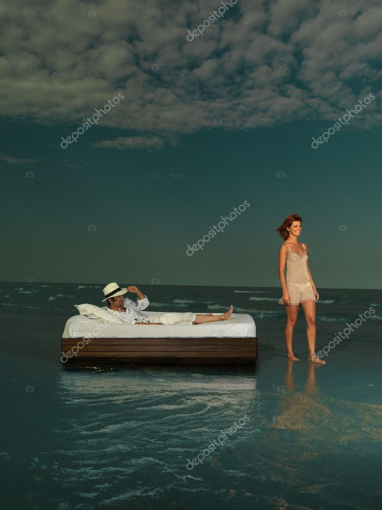 Young couple laying bed surrounded by sea