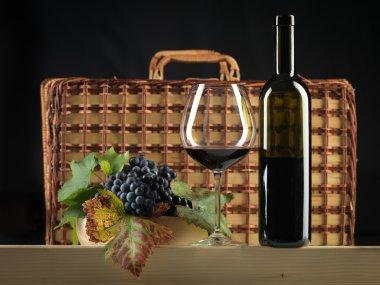 Red wine bottle, glass, grapes, picnic basket