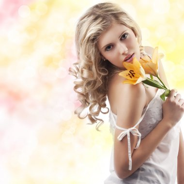 Blond curly woman holding lily
