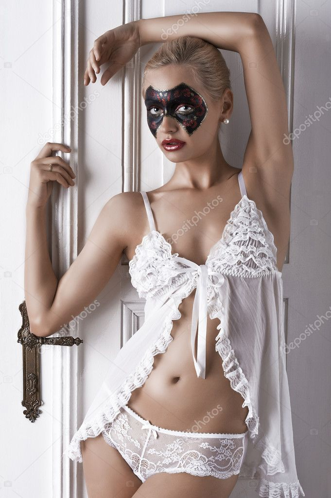 1376bb7848 Half body shot of a blonde posing in a doorway wearing white lingerie and a  painted carnival mask on her face — Photo by carlodapino
