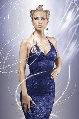 Elegant blonde model wearing a blue dress and make up