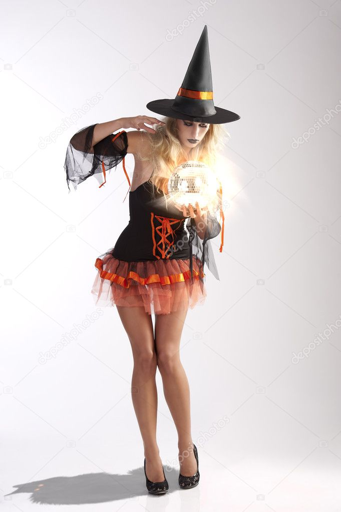 Very sexy and beautiful young woman with black and orange witch dress  holding magical ball looking for future — Photo by carlodapino ea17f2852525