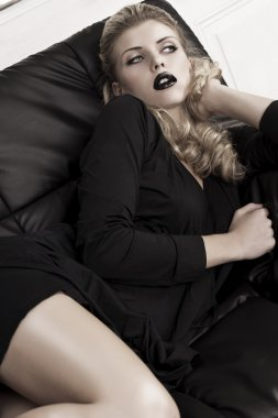 Sensual blonde girl laying on a couch