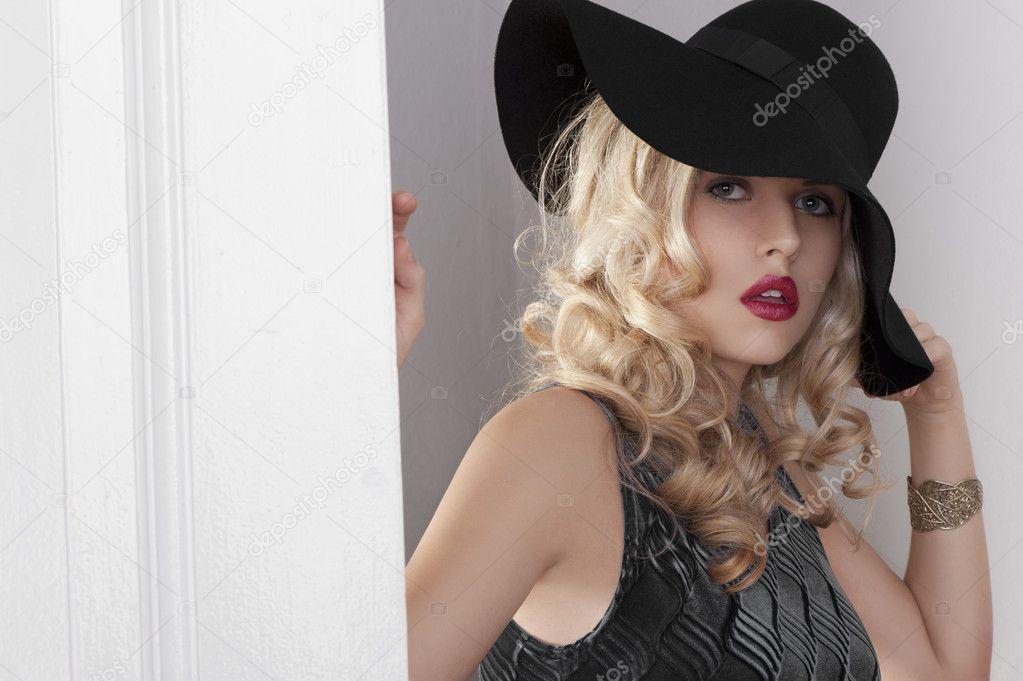 50a9de915748 Ritratto di ragazza bionda bella con i capelli ricci e cappello con abito  blu nei pressi di una vecchia porta di moda bianca guardando la telecamera  — Foto ...