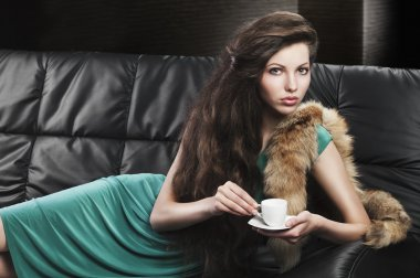 Young elegant girl in green with cup, she looks in to the lens