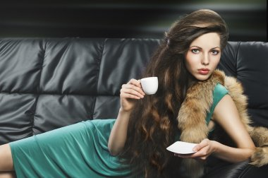 Young elegant girl in green with cup, she is lying on the sofa