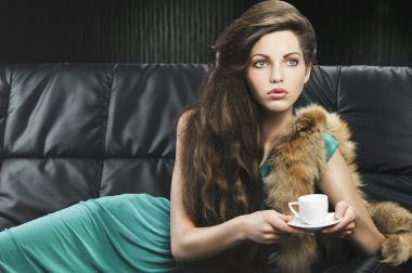 Young elegant girl in green with cup, she is in front of the len