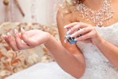 Hands of the bride and a bottle of perfume