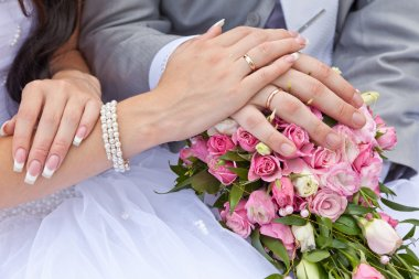 Hands of the groom and the bride on a wedding bouquet