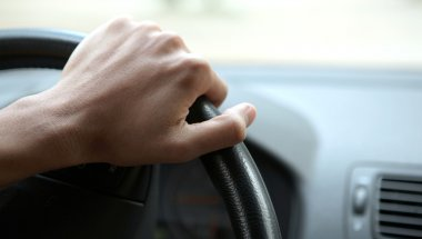 Close-up of a male hand on steering wheel in a modern car in the