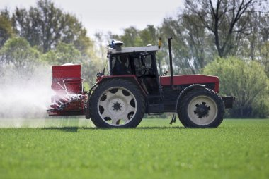 Tractor spraying a filed with pesticides/fertilizers